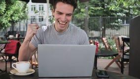 Equipe a datilografia no portátil ao sentar-se no terraço do café video estoque