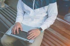 Equipe a datilografia no portátil e o assento no banco fora imagens de stock