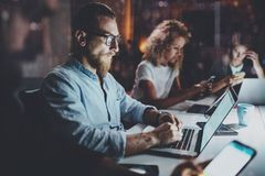 A equipe de colegas de trabalho novos trabalha junto no escritório da noite Jovens que usam dispositivos eletrônicos na tabela ho Imagem de Stock Royalty Free