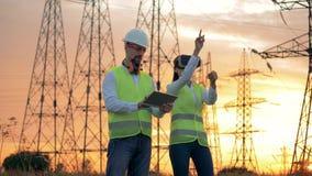 A equipe de coordenadores industriais trabalha perto da linha elétrica usando a tecnologia de 3D VR