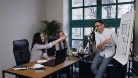 Equipe de coordenadores novos durante o dia do trabalho no escritório de arquiteto filme