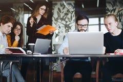A equipe de coordenadores novos está pensando sobre um projeto, discutindo Imagens de Stock Royalty Free