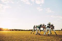 Equipe de futebol americana que faz brocas defensivas durante uma prática imagem de stock
