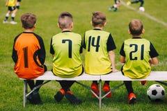 Equipe de futebol das crianças que senta-se em um banco Futebol Team Players das crianças Fotografia de Stock Royalty Free