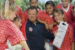 Equipe de futebol das meninas de Discussing Strategy With do treinador imagens de stock