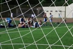 Equipe de futebol de descanso. olhe a rede do objetivo da calha. Fotos de Stock