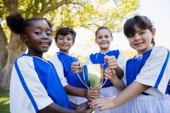 Equipe de futebol feliz das crianças que guarda o copo fotografia de stock