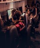 A equipe de gamers adolescentes joga em um jogo de vídeo para múltiplos jogadores no PC em um clube do jogo imagens de stock