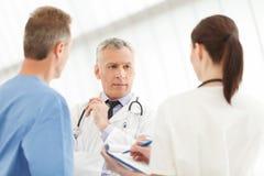 Equipe de inquietação de profissionais médicos dos cuidados médicos. Três doutores d fotografia de stock