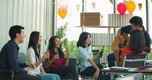 A equipe de jovens comemora com o brinde e o tinido que aumentam vidros em seu escritório filme