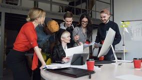 Equipe de multi étnico dos povos novos do moderno que discutem ideias do negócio com o chefe fêmea atrativo ao sentar-se em filme
