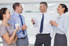 Equipe de sorriso do trabalho durante o tempo da ruptura imagem de stock royalty free
