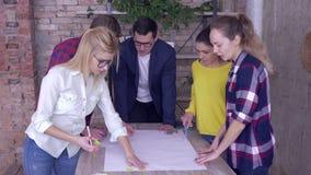 Equipe de trabalho bem sucedida no escritório moderno, homem novo do chefe com os associados que discutem no projeto de desenvolv