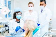 Equipe dental multirracial com o paciente na clínica dental Conceito dental da saúde fotografia de stock