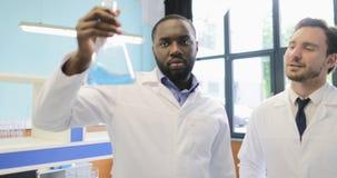 A equipe diversa dos cientistas que analisam o líquido na garrafa que trabalha no laboratório que faz experiências mistura o grup video estoque