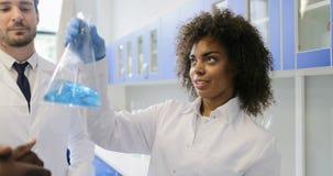 A equipe diversa dos cientistas que analisam o líquido na garrafa que trabalha no laboratório que faz experiências mistura o grup filme