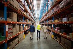 Equipe do armazém que discute ao andar no armazém imagens de stock