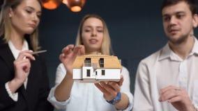 Equipe do arquiteto novo que discute o modelo 3d da casa vídeos de arquivo