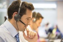 Equipe do centro de atendimento no escritório no telefone com auriculares Fotos de Stock Royalty Free