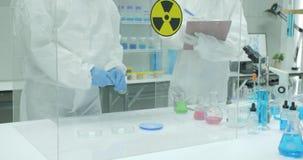 Equipe do cientista que trabalha em um laboratório de pesquisa de nível elevado seguro video estoque