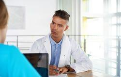 Equipe do doutor e da enfermeira que discutem um diagnóstico paciente que senta-se na mesa no escritório moderno brilhante fotos de stock