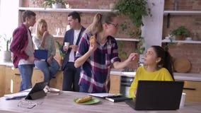 A equipe do escritório de sócios comerciais novos bem sucedidos é comendo e de trabalho com tabuletas e portáteis na cozinha dura