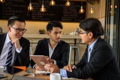 A equipe do homem de negócios discute o projeto no café do café Imagens de Stock Royalty Free