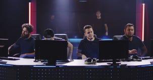 Equipe do jogo que senta-se para baixo em computadores filme
