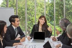 Equipe do negócio asiático que levanta na sala de reunião Sessão de reflexão de trabalho na tabela em uma sala Povos asiáticos Ho foto de stock