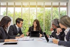 Equipe do negócio asiático que levanta na sala de reunião Sessão de reflexão de trabalho na tabela em uma sala Povos asiáticos Ho fotografia de stock