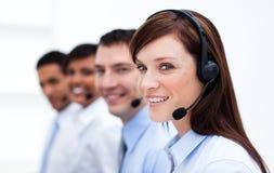 Equipe do negócio com auriculares sobre em um centro de chamadas Fotografia de Stock Royalty Free