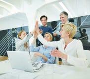 Equipe do negócio com o computador que dá a elevação cinco Imagem de Stock Royalty Free
