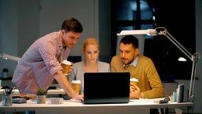 Equipe do negócio com o computador que trabalha tarde no escritório video estoque