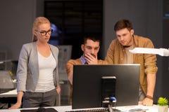 Equipe do negócio com o computador que trabalha tarde no escritório fotografia de stock
