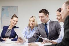 Equipe do negócio com o PC da tabuleta que tem a discussão Fotografia de Stock Royalty Free