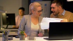 Equipe do negócio com o portátil que trabalha no escritório da noite filme