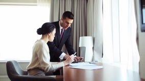 Equipe do negócio com papéis e PC da tabuleta no hotel filme