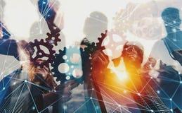 A equipe do negócio conecta partes de engrenagens Trabalhos de equipa, parceria e conceito da integração com efeito da rede dobro imagem de stock royalty free