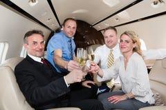 Equipe do negócio dos vidros do tim-tim dos elogios em um jato incorporado que bebe c Imagem de Stock