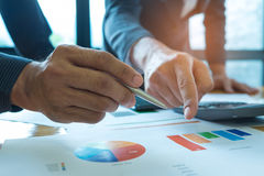 A equipe do negócio está analisando uns dados dos gráficos com portáteis e calc Foto de Stock