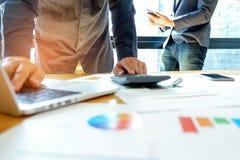 A equipe do negócio está analisando uns dados dos gráficos com portáteis e calc imagem de stock royalty free