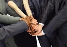 A equipe do negócio, isolada no fundo branco pôs nas mãos de um lugar em um sinal da unidade e da amizade Fotografia de Stock