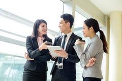 Equipe do negócio que discute algo no tablet pc Imagem de Stock
