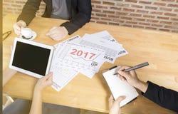 A equipe do negócio que discute analisa o planeamento financeiro da previsão da tendência do ano 2017 do gráfico do relatório na  Imagem de Stock