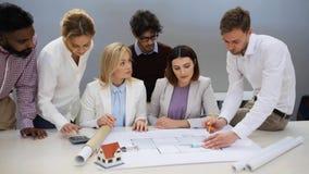 Equipe do negócio que discute o projeto da casa no escritório filme
