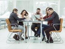 Equipe do negócio que discute os originais de trabalho que sentam-se atrás de uma mesa Fotos de Stock Royalty Free