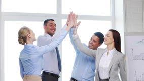 Equipe do negócio que faz o gesto da elevação cinco no escritório filme