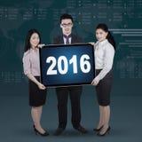 Equipe do negócio que guarda os números 2016 em uma placa Fotos de Stock Royalty Free