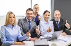 Equipe do negócio que mostra os polegares acima no escritório fotografia de stock royalty free