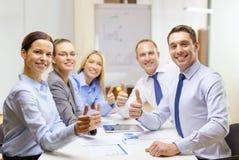 Equipe do negócio que mostra os polegares acima no escritório imagens de stock